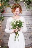 Junge rothaarige Braut in einem grünen Kranz unter dem Bogen von Herbstpflanzen Stockfoto