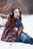 Junge rothaarige Frau Dreamly, die ein heißes Getränk von einem Becher im Winterpark trinkt Stockfotografie