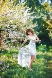 Junge rothaarige Frau in einem weißen Sommerkleid im blühenden Garten, nahe bei einem Baum Lizenzfreies Stockfoto