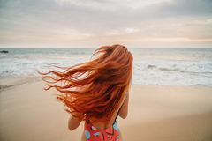 Junge rothaarige Frau mit dem Fliegenhaar auf dem Ozean, hintere Ansicht stockfotografie