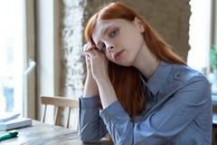Junge rothaarige Studentinfrau, die für Prüfungen am c sich vorbereitet stockfoto