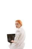 Junge Rothaarigefrau, die einen Laptop verwendet Stockfotografie