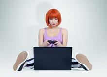 Junge Rothaarigefrau mit Steuerknüppel sitzt auf dem Boden vor einem Laptop Gamerspiele lizenzfreies stockbild
