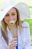 Junge ruhige blonde Frau, die eine weiße Blume riecht Lizenzfreies Stockbild