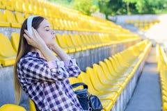 Junge ruhige Frau im karierten Hemd hörend Musik am Th stockbild