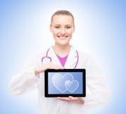 Junge Ärztin, die eine Tablette hält Stockfotografie