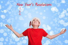 Junge in Sankt-Hut, der aufwärts auf Feiertag Weihnachtshintergrund schaut Stockbilder