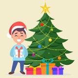 Junge in Santa Claus-Hut, der nahe verzierten Weihnachtsbaum wi steht Stockbild