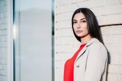 Junge schöne brunette Frauenstellung des Porträts nahe weißem Backsteinmauerfreien im städtischen Hintergrund stockfotografie