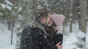 Junge schöne kaukasische Paare, die zusammen unter einem Schnee ein in den Winterwaldmodernen millennials haben Spaß küssen stock video footage