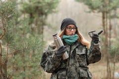 Junge schöne überraschte blonde Frau in der Tarnungsausstattung und in grünem Schal, die mit Thermosflasche im Wald, zeigend auf  Stockfotos