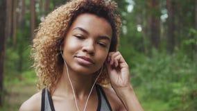 Junge schöne afro-amerikanische Frau mit dem gelockten Haar setzt an Kopfhörer ein, bevor sie in Wald rüttelt stock video footage