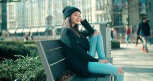 Junge schöne Afroamerikanerfrau, die auf einer Bank sitzt Lizenzfreies Stockbild