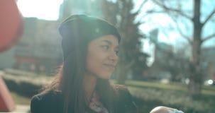 Junge schöne Afroamerikanerfrau, die auf einer Bank sitzt Lizenzfreie Stockfotos