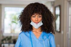 Junge schöne Afroamerikanerfrau mit medizinischer Kleidung stockfotos