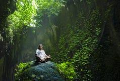 Junge schöne Asiatin-übendes Yoga, welches das Sitzen im Lotussitz meditiert über einem Stein in einem erstaunlichen natürlichen  stockbilder