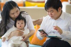 Junge schöne asiatische chinesische Familie, die am modernen Erholungsort mit dem Workaholicmannarbeitsgeschäft on-line mit digit stockfotos