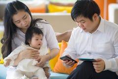 Junge schöne asiatische chinesische Familie, die am modernen Erholungsort mit dem Workaholicmannarbeitsgeschäft on-line mit digit lizenzfreie stockfotos