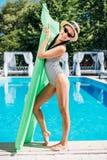 Junge schöne asiatische Frau, die mit aufblasbarer Matratze am Poolside aufwirft lizenzfreie stockfotos