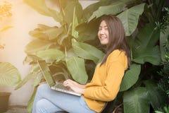 Junge schöne asiatische Frau, die mit Laptop Park am im Freien arbeitet, lizenzfreie stockfotos