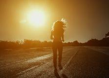 Junge, schöne, athletische Frau mit dem langen gelockten Haar läuft morgens auf dem Hintergrund des Sonnenaufgangs Lizenzfreies Stockbild