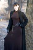 Junge schöne attraktive Frau im Kleid und im Mantel Stockfoto