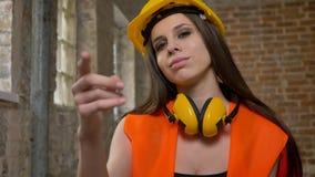 Junge schöne attraktive Frauen im Sturzhelm und Kopfhörer, die in camera zeigen und jemand, weiblichen Erbauer, Ziegelstein einla stock video