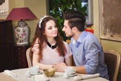 Junge schöne bezauberte Paare, die an einem Tisch in einem Café sitzen Lizenzfreies Stockfoto