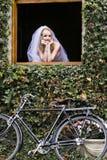 Junge schöne blonde Braut, die heraus Fenster schaut Stockfotografie