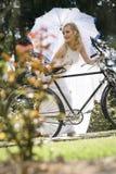 Junge schöne blonde Braut mit Weinlesefahrrad Stockbild