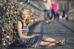 Junge schöne blonde Frau, die auf der Brücke der Liebe sitzt Lizenzfreies Stockbild
