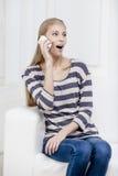 Junge schöne blonde Frau, die auf der Couch sitzt Stockfoto