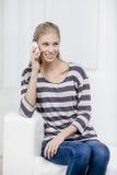Junge schöne blonde Frau, die auf der Couch sitzt Stockbild