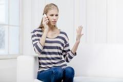 Junge schöne blonde Frau, die auf der Couch sitzt Lizenzfreies Stockfoto