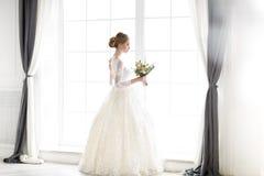 Junge schöne blonde Frau, die in einem Hochzeitskleid aufwirft Lizenzfreie Stockfotografie