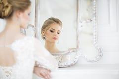 Junge schöne blonde Frau, die in einem Hochzeitskleid aufwirft Stockfoto