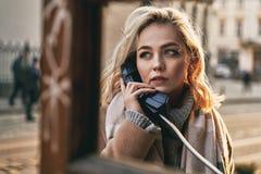 Junge schöne blonde Frau, die einen wichtigen Anruf in einer allgemeinen Telefonzelle der Weinlese an einem sonnigen Abend macht stockfotografie