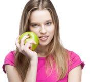 Junge schöne blonde Frau, die grünen Apfel hält Stockbilder