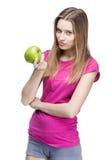 Junge schöne blonde Frau, die grünen Apfel hält Stockfotos
