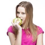 Junge schöne blonde Frau, die grünen Apfel isst Stockfoto
