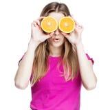 Junge schöne blonde Frau, die Orange hält Stockfoto