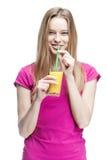 Junge schöne blonde Frau, die Orangensaft trinkt Stockfotos