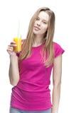 Junge schöne blonde Frau, die Orangensaft trinkt Lizenzfreie Stockbilder