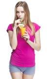 Junge schöne blonde Frau, die Orangensaft trinkt Stockbild