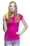 Junge schöne blonde Frau, die Orangensaft trinkt Stockbilder