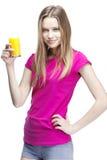 Junge schöne blonde Frau, die Orangensaft trinkt Stockfotografie