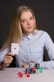 Junge schöne blonde Frau, die Poker über Grau spielt Stockfoto