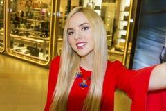 Junge schöne blonde Frau, die selfie mit Handy nimmt Stockbild
