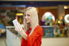 Junge schöne blonde Frau, die selfie mit Handy nimmt Lizenzfreie Stockfotos