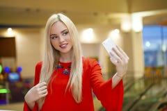 Junge schöne blonde Frau, die selfie mit Handy nimmt Lizenzfreie Stockfotografie